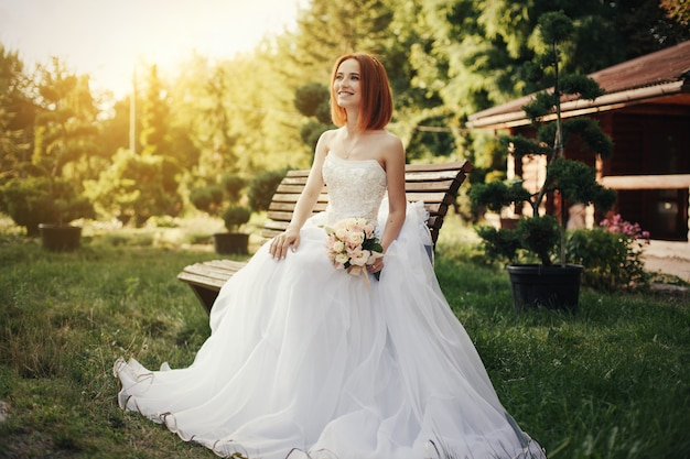 Bride in elegant wedding gown sits on stone bench