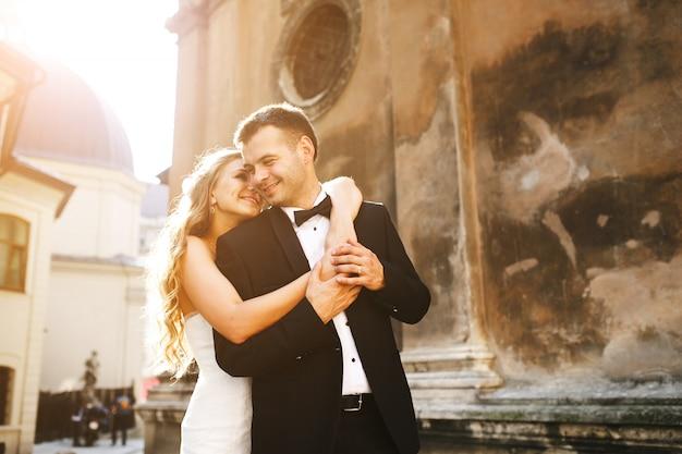 Bride embracing her boyfriend from behind