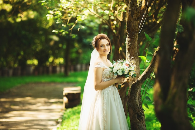Bride in fashion wedding dress on natural background. a beautiful woman portrait in the park