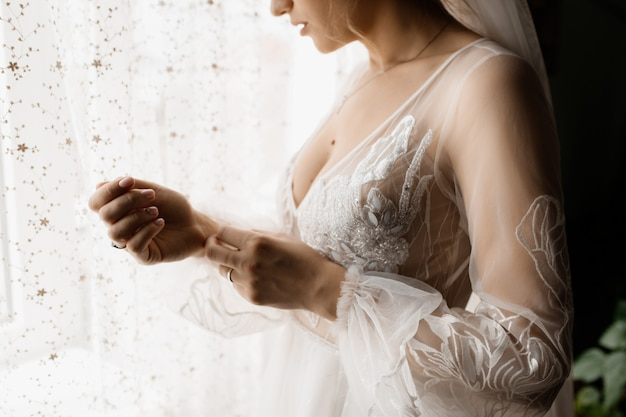 Bride fastens a button on her dress sleeve