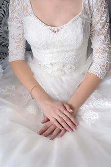 Невеста сложила нежные руки на белом красивом платье