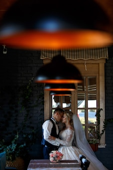 Bride gently embraces the groom indoor. emotional newlyweds hugging near the window. smiling wedding couple in a room with a stylish interior with lamps. wedding day