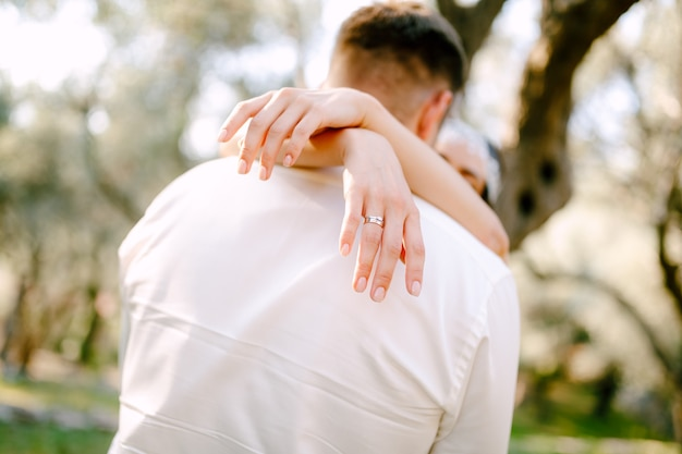 The bride gently hugs the groom in the park, wrapping her arms around his neck, close-up