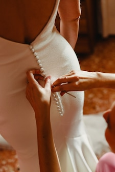 Bride getting ready, they help her by buttoning the buttons on the back of her dress.
