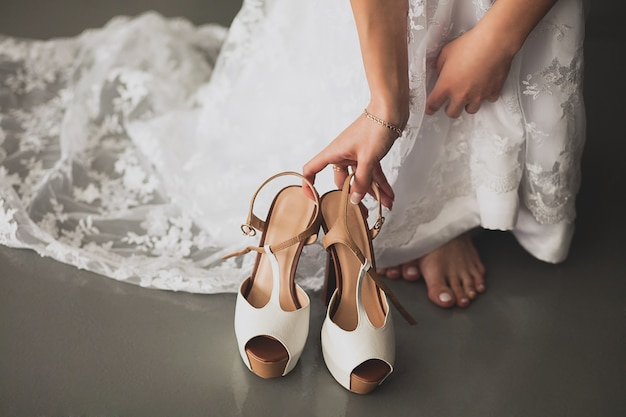 The bride, girl or young woman in a beautiful elegant modern stylish wedding dress reaches for light fashionable high-heeled shoes to put on, close-up. the day of the wedding or the morning.