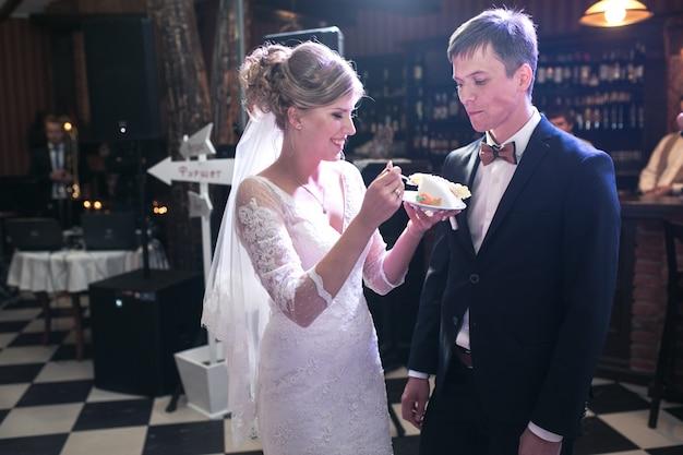 Bride giving boyfriend a piece of cake