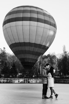Bride and groom against the background of a frozen lake and a balloon flying in a city park.