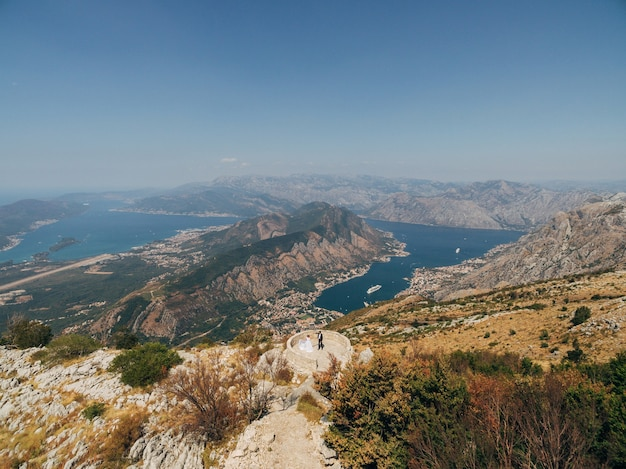 The bride and groom are dancing on the observation deck on mount lovcen overlooking the bay of kotor