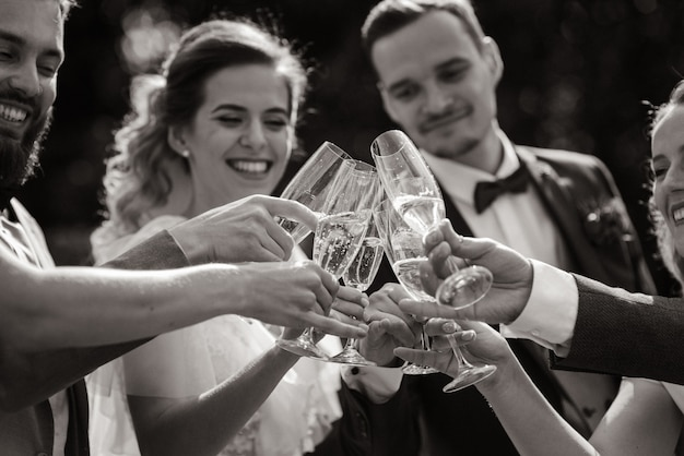 Bride and groom are drinking champagne with best friends outdoors with sincere smiles, monochrome view