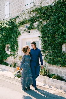 The bride and groom are embracing along the road near an old building with a white door the wall is