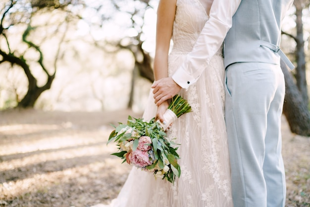 The bride and groom are embracing among the trees the bride holds bridal bouquet closeup