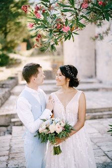 The bride and groom are embracing under a blooming oleander the bride is holding a bouquet in her