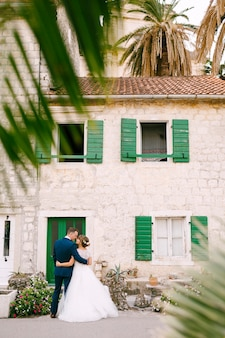 The bride and groom are embracing in front of a beautiful white house with green doors and shutters