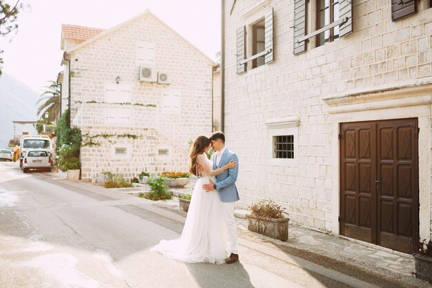 The bride and groom are embracing near the beautiful white houses in the old town of perast