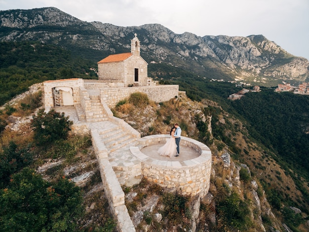 The bride and groom are embracing on the observation deck near an ancient monastery in the mountains