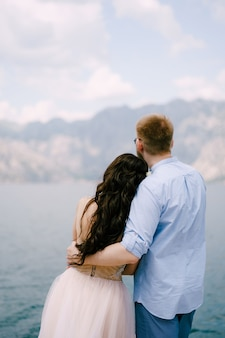 The bride and groom are embracing on the pier in the bay of kotor back view