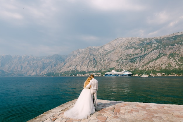 The bride and groom are embracing on the pier in the bay of kotor a cruise ship is sailing in front