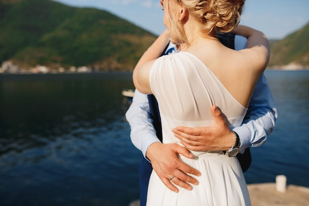 The bride and groom are embracing on the pier in perast, the groom put his hands on the bride's waist . high quality photo