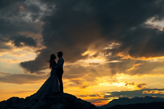 The bride and groom are embracing on the rocks in the mountains at sunset silhouettes
