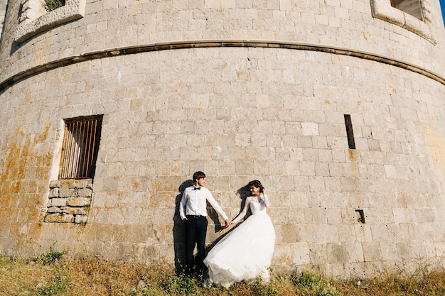 Bride and groom are holding hands and standing together near the wall of the arza fortress