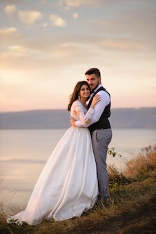 The bride and groom are hugging on the background of the lake during sunset
