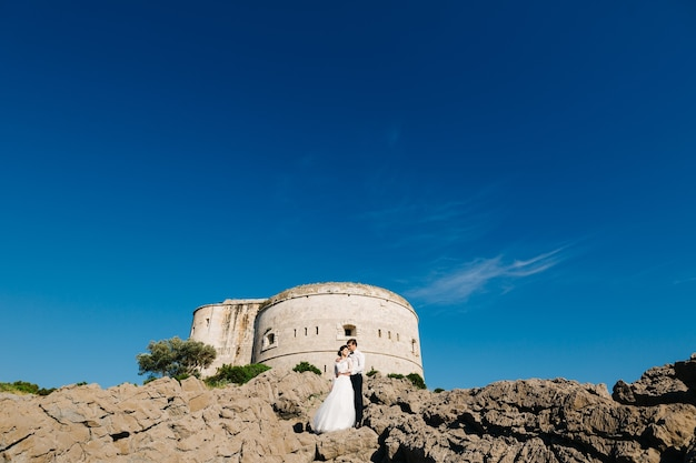 Bride and groom are hugging near the arza fortress on the mamula island.