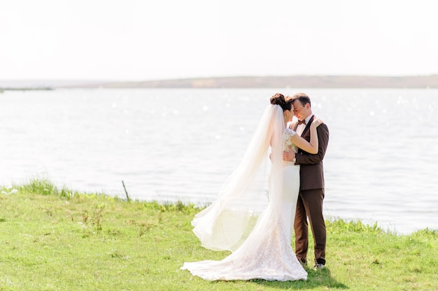 The bride and groom are hugging near the pond in nature. the wind raises a light veil.
