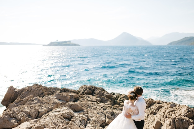 Bride and groom are hugging on the rocky beach of the mamula island near arza fortress.