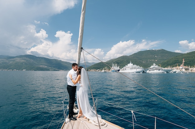 The bride and groom are hugging while standing on the bow of a white yacht sailing in the bay of
