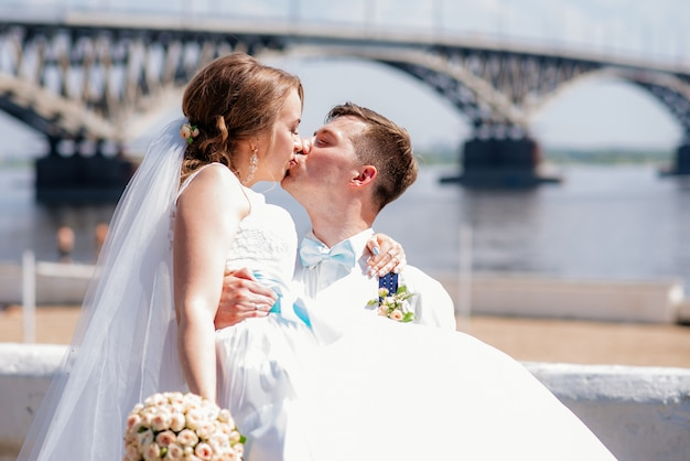 The bride and groom are photographed on the background of the bridge