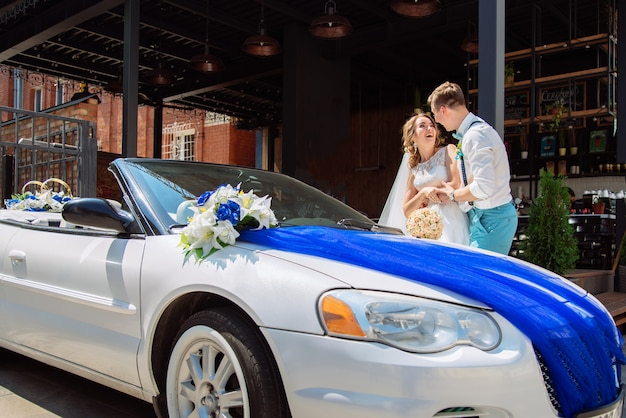 The bride and groom are photographed near the car