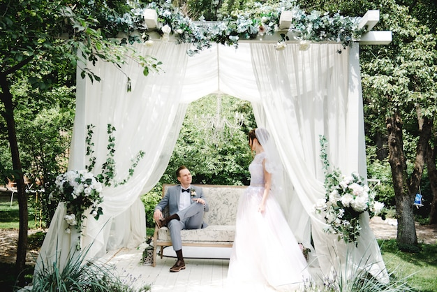 The bride and groom are sitting on a beautiful couch in a gazebo in the garden.