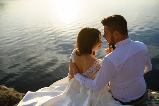 The bride and groom are sitting on the edge of a cliff against the backdrop of the lake