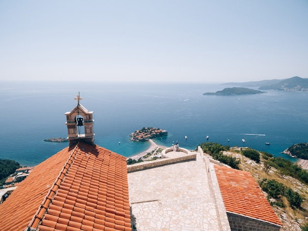 The bride and groom are sitting embracing on the observation deck overlooking the island of sveti
