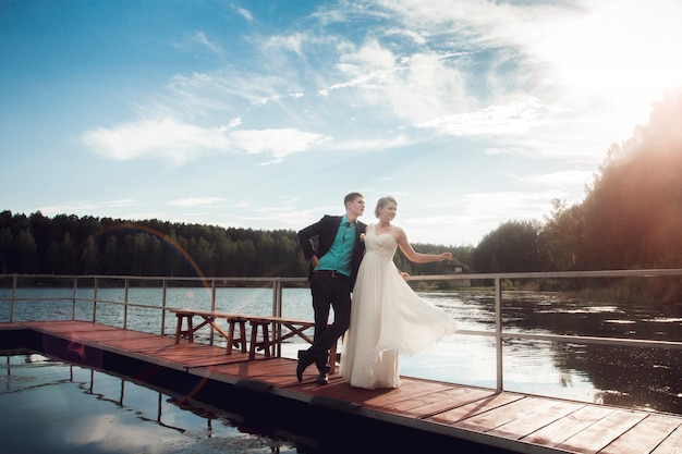 Bride and groom are standing on the bridge at the lake. the couple of newlyweds