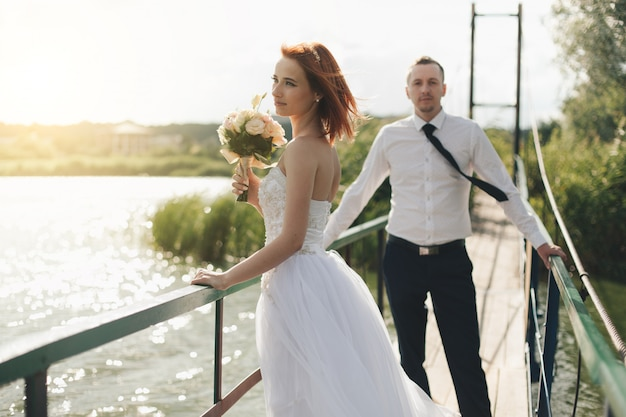 Bride and groom are standing on the bridge