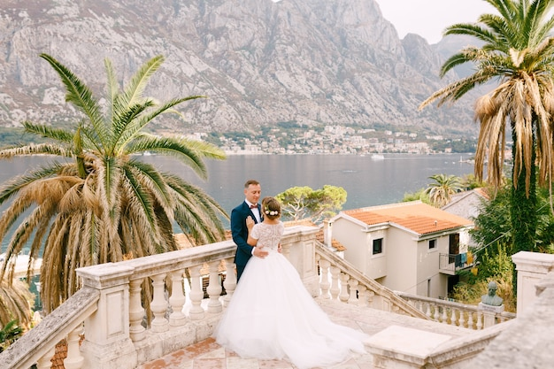 The bride and groom are standing and hugging on the staircase in the old city behind them is