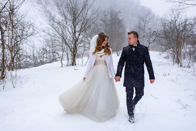 The bride and groom are walking by the hand against the backdrop of a winter forest. snowing.