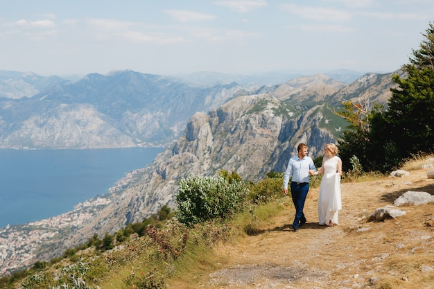 The bride and groom are walking hand in hand along the road, behind them is a panoramic view of the bay of kotor. high quality photo