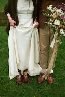 Bride and groom in autumn boots on the grass, showing legs