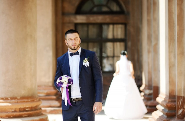 The bride and groom on the background of an old building with columns