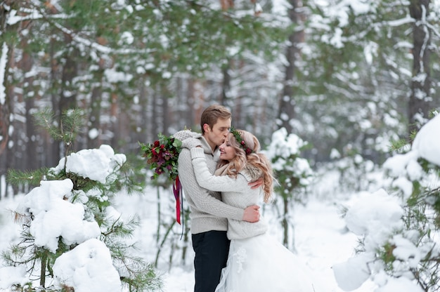 Bride and groom in beige knitted pullovers in snowy forest. newlyweds is touching foreheads. winter wedding. copy space