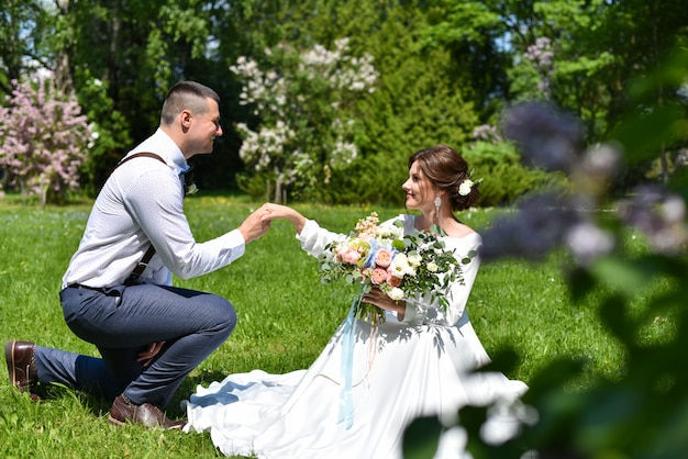 Bride and groom in a bouquet are walking in a green park