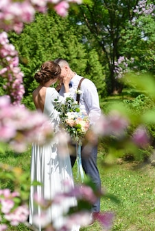 Bride and groom in a bouquet kiss in a green park