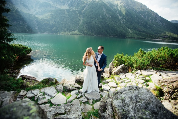 The bride and groom closed their eyes and hugging each other on beautiful landscape