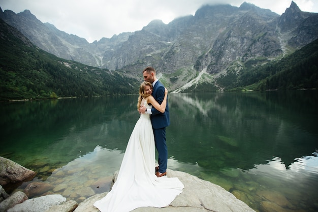 The bride and groom closed their eyes and hugging each other in beautiful landscape