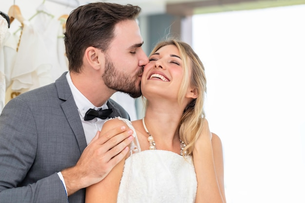 Bride and groom couple of caucasian kiss and hug in wedding studio.