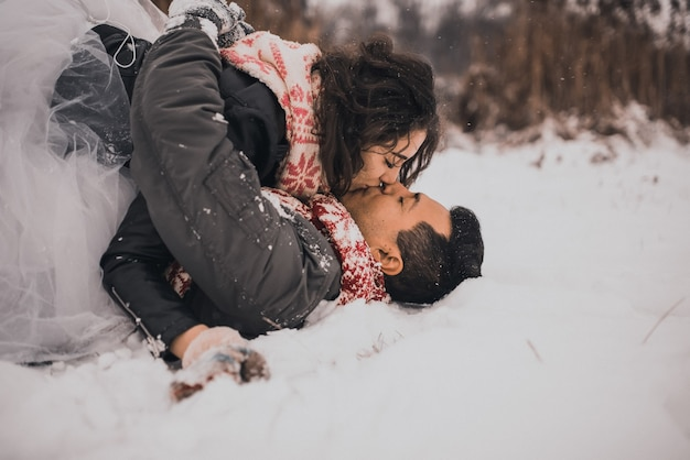 Bride and groom couple in knitted scarf and mittens in winter and snowflakes