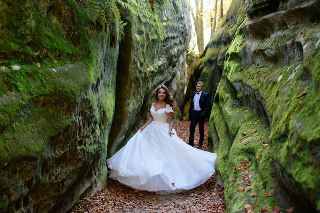 Bride and groom. a couple strolling among the narrow beautiful gorge. the gorge was overgrown with green moss. the newlyweds are spinning and running