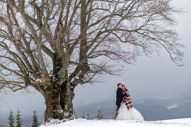 The bride and groom cuddle under a rug to keep warm. winter wedding